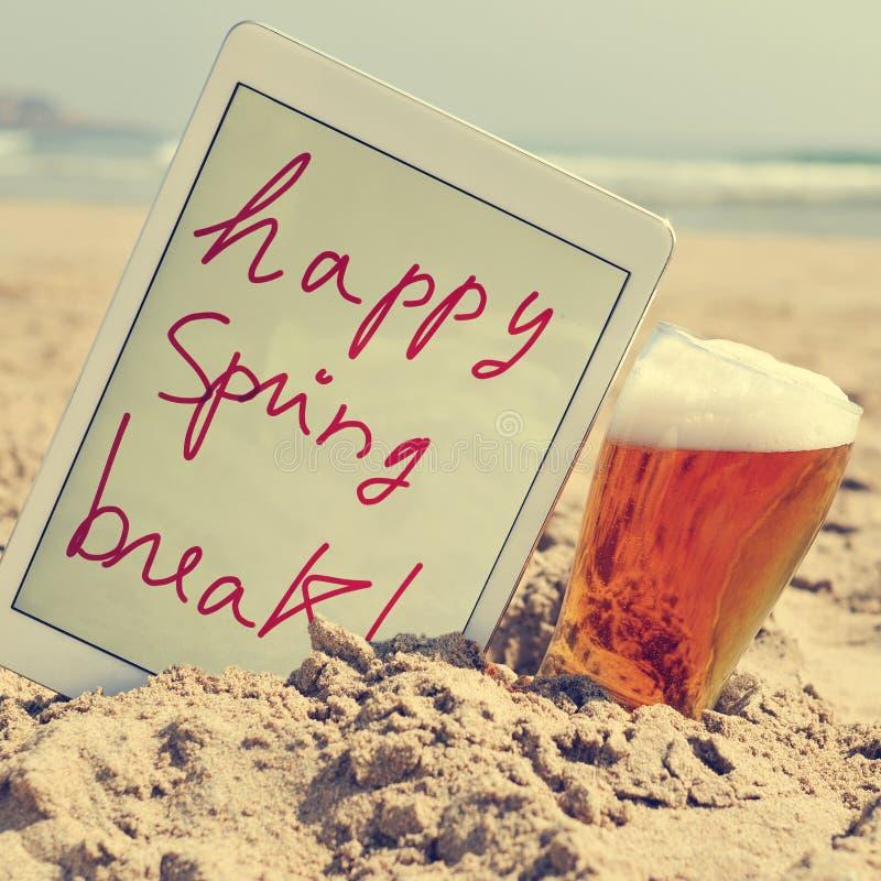 Una birra e la molla felice del testo irrompono una compressa sulla spiaggia, fotografia stock libera da diritti