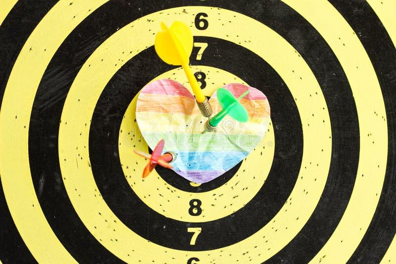 Una blanco con los dardos en el centro cuyo el corazón arrugado de LGBT, matrimonios homosexuales imágenes de archivo libres de regalías