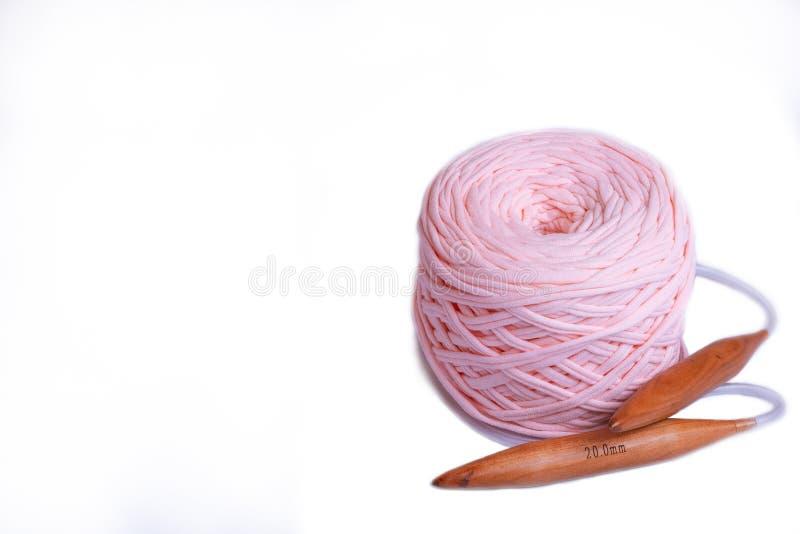 Una bobina di grande filato tricottato di colore della pesca con gli aghi di bambù circolari da 20 millimetri su fondo bianco, is immagini stock
