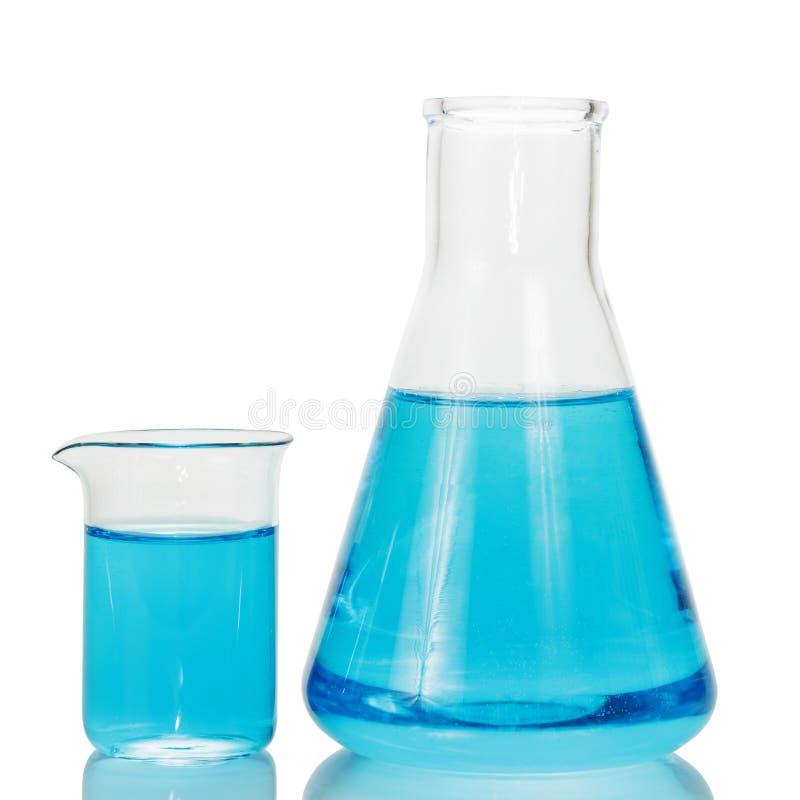Una boccetta e un becher chimici con i liquidi blu isolati su bianco immagine stock