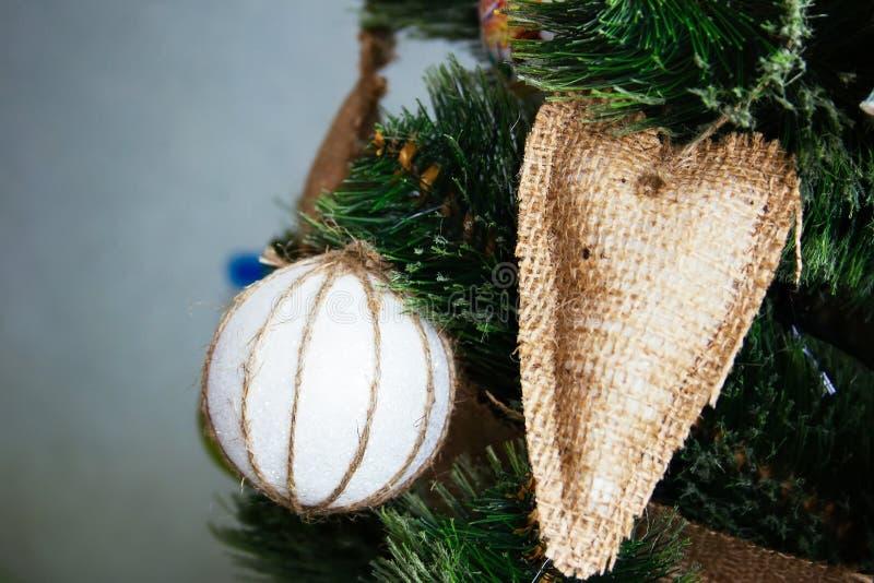 Una bola blanca envuelta en un cordón encerado y un corazón cosido de caída de despido en un árbol de navidad artificial adornado imagen de archivo
