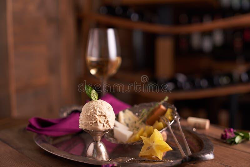 Una bola del helado del caramelo con una hoja de la menta en un cuenco del helado con la fruta del carambola en el fondo de una p imágenes de archivo libres de regalías