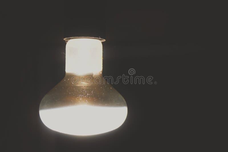 Una bombilla ilumina un cuarto oscuro imágenes de archivo libres de regalías