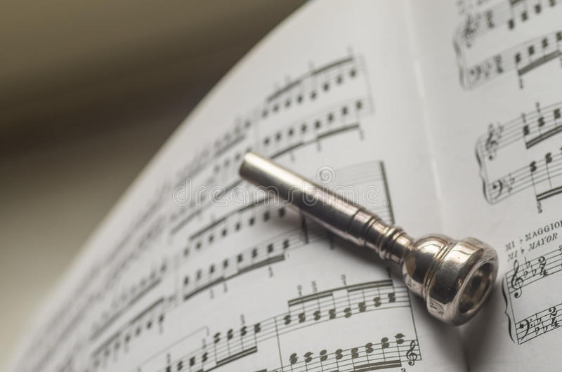 Una boquilla de plata de la trompeta en el libro de partitura fotografía de archivo libre de regalías