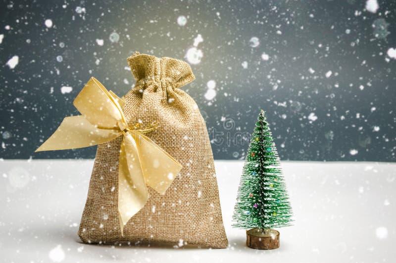 Una borsa di soldi con l'albero di Natale Natale acquisto e preparare per la festa L'accumulazione di soldi per i regali nuovo immagini stock