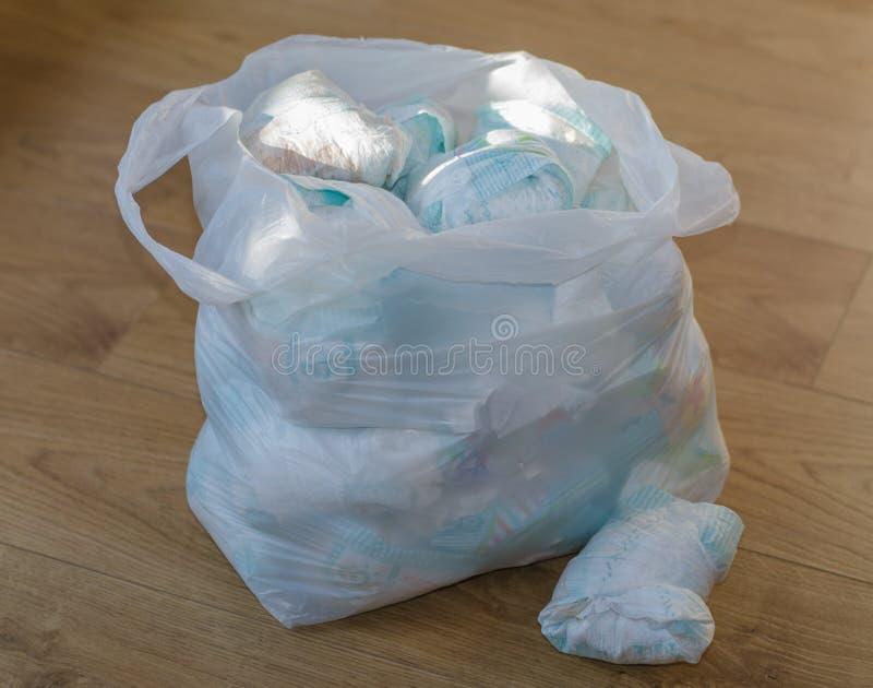 Una borsa in pieno dei pannolini sporchi del ` s del bambino che stanno sul pavimento fotografie stock