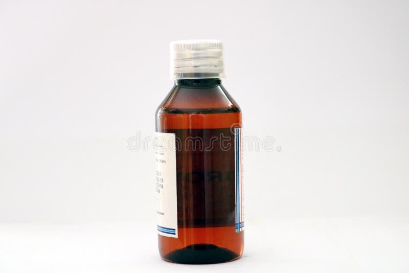 Una botella ambrina del animal doméstico de la medicina con el casquillo transparente de la dosificación imagen de archivo