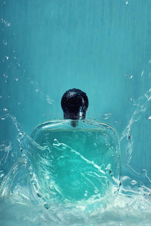 Una botella con perfume en un fondo azul con salpica del agua esa mosca en todas las direcciones imágenes de archivo libres de regalías
