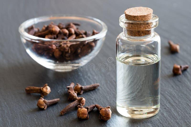 Una botella de aceite esencial del clavo con los clavos secados fotos de archivo libres de regalías