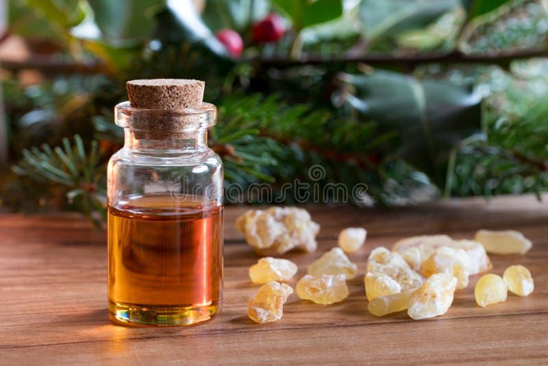 Una botella de aceite esencial del incienso con la resina del incienso foto de archivo libre de regalías