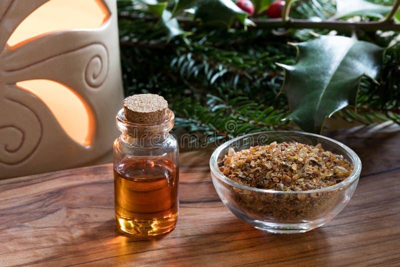 Una botella de aceite esencial de la mirra con la resina de la mirra en un bott de cristal fotos de archivo