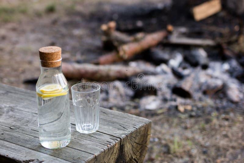 Una botella de agua con el limón y un vidrio Hoguera extinguida i fotografía de archivo