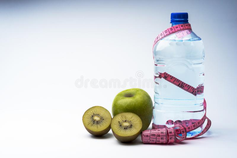 Una botella de agua mineral con un centímetro y de Apple con el kiwi fotografía de archivo libre de regalías