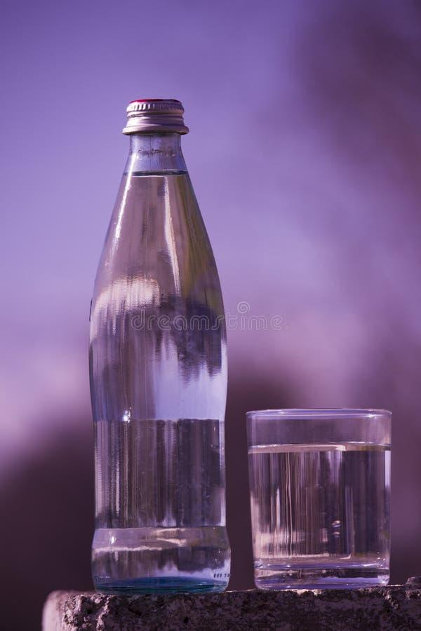 Una botella de agua potable y de soportes de cristal contra la perspectiva de una violeta imagen de archivo