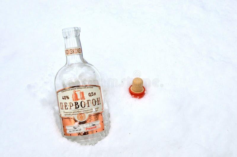 """Una botella de alcohol en la nieve blanca el  del """"Pervogon†es una bebida alcohólica fuerte bielorrusa tradicional, preparad fotos de archivo libres de regalías"""