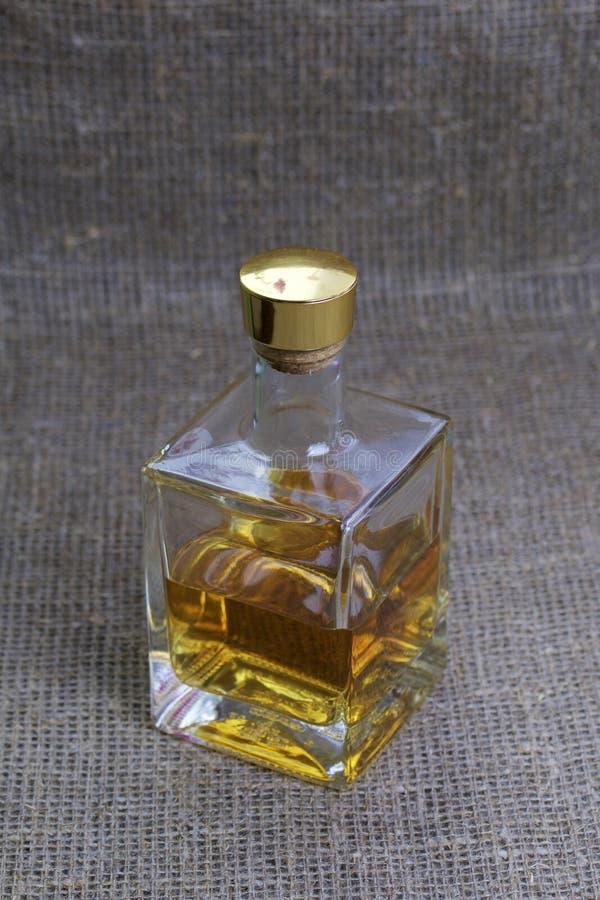 Una botella de alcohol fuerte Del vidrio transparente, una forma cuadrada fotos de archivo