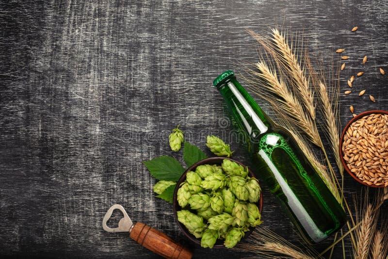 Una botella de cerveza con saltos, espiguillas, avena del cuenco y abrelatas verdes en un tablero de tiza rasguñado negro imagenes de archivo