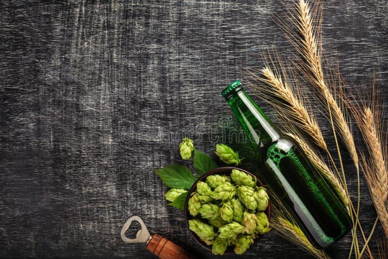 Una botella de cerveza con saltos, espiguillas y abrelatas verdes en un tablero de tiza rasguñado negro imágenes de archivo libres de regalías