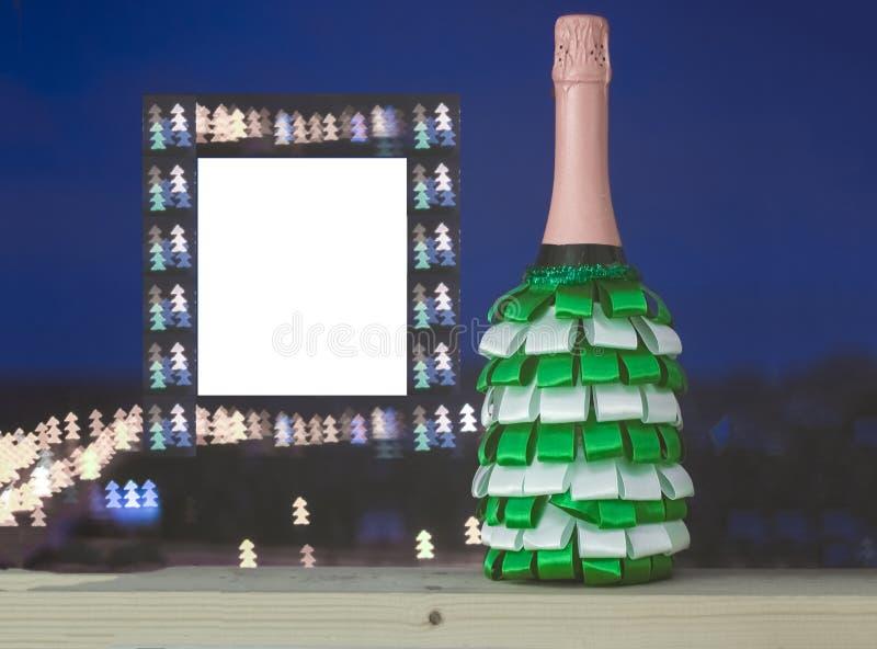 Una botella de champán adornada con las cintas de verde y de blanco imágenes de archivo libres de regalías