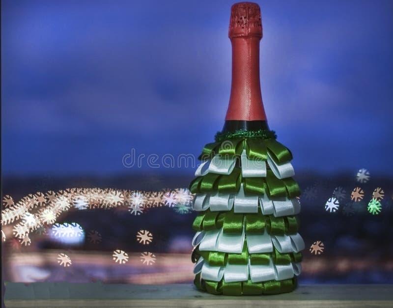 Una botella de champán adornada con las cintas de verde y de blanco imagenes de archivo