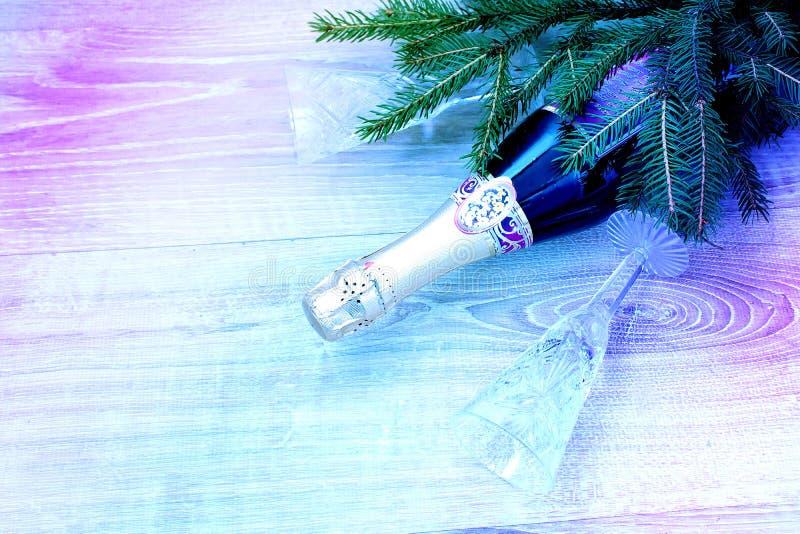 Una botella de champán y de dos cristales vacíos foto de archivo