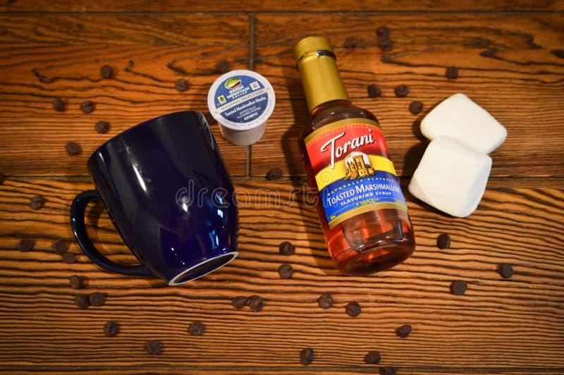 Una botella de jarabe de la condimentación de la melcocha Toasted para el café, una taza de café de los azules marinos, el café c fotografía de archivo libre de regalías