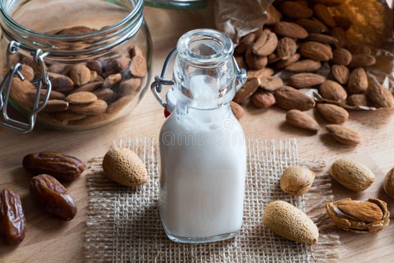 Una botella de leche de la almendra con las almendras y las fechas fotografía de archivo