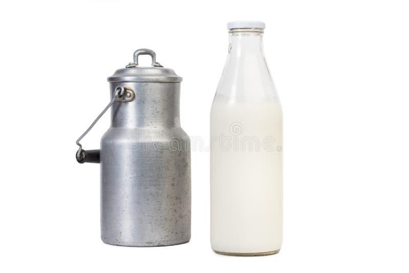 Una botella de leche y de un jarro de leche viejo imagen de archivo