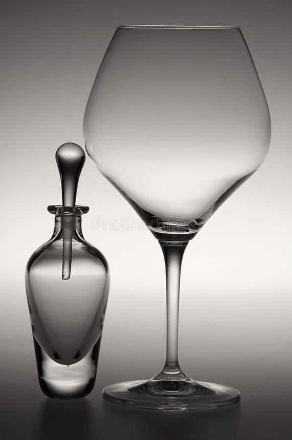Una botella de perfume y una copa de vino fotografía de archivo