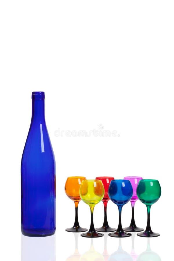 Una botella de vidrio azul y seis coloreó los vidrios foto de archivo libre de regalías