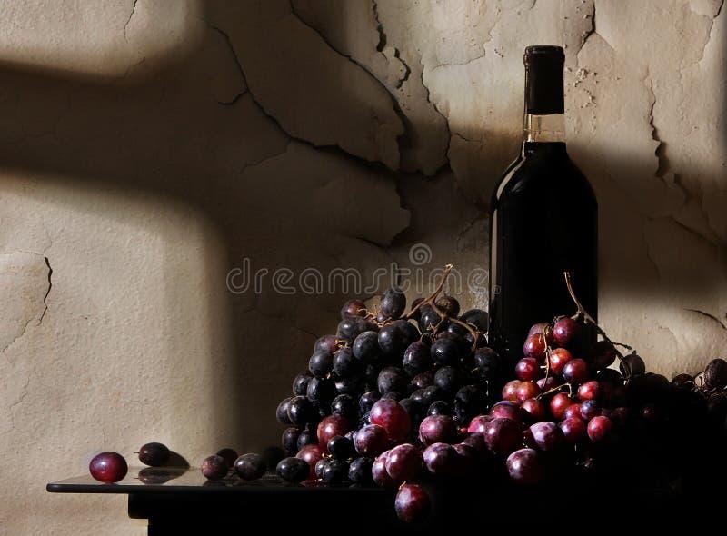 Una botella de vino con las uvas de vino se ve delante de la pintura envejecida y de peladura en esta fotografía iluminada por el fotografía de archivo