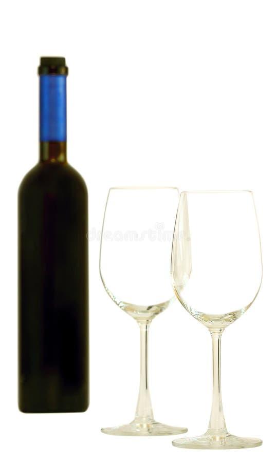 Una botella de vino rojo y de vidrios imagen de archivo