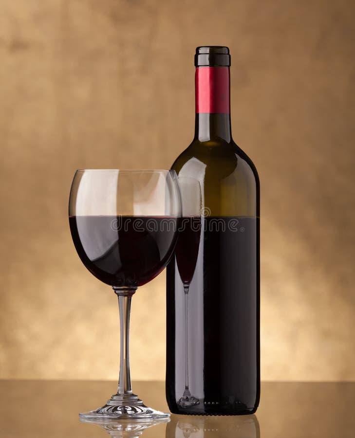 Una botella de vino rojo y llenada un vidrio de vino foto de archivo