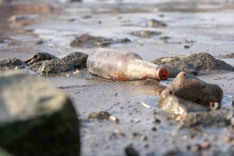 Una botella marrón desesperada lavada para arriba en la orilla foto de archivo