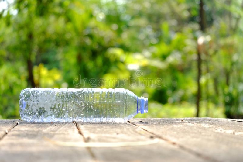 Una botella plástica de agua potable que deja en desorden en la tabla de madera vieja en el parque público con el fondo verde de  imagenes de archivo