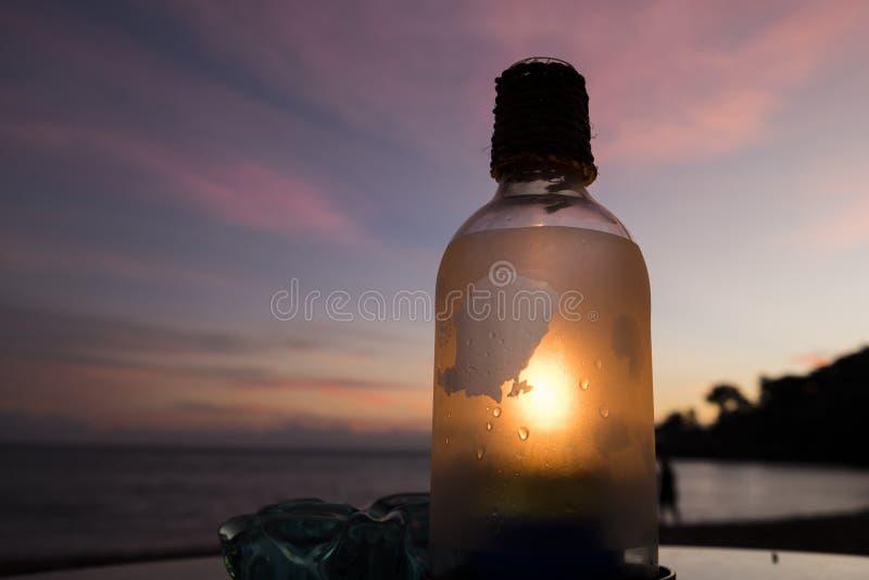 Una bottiglia con il cielo porpora fotografie stock