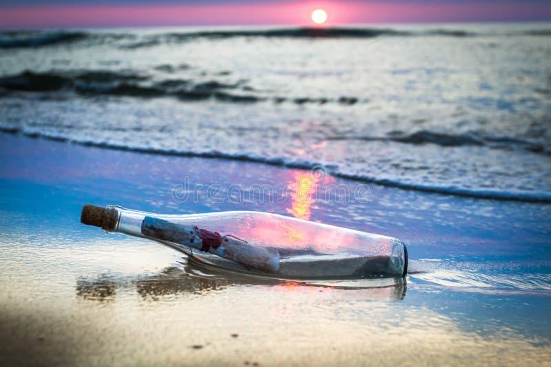 Una bottiglia con un messaggio gettato dal mare fotografia stock libera da diritti