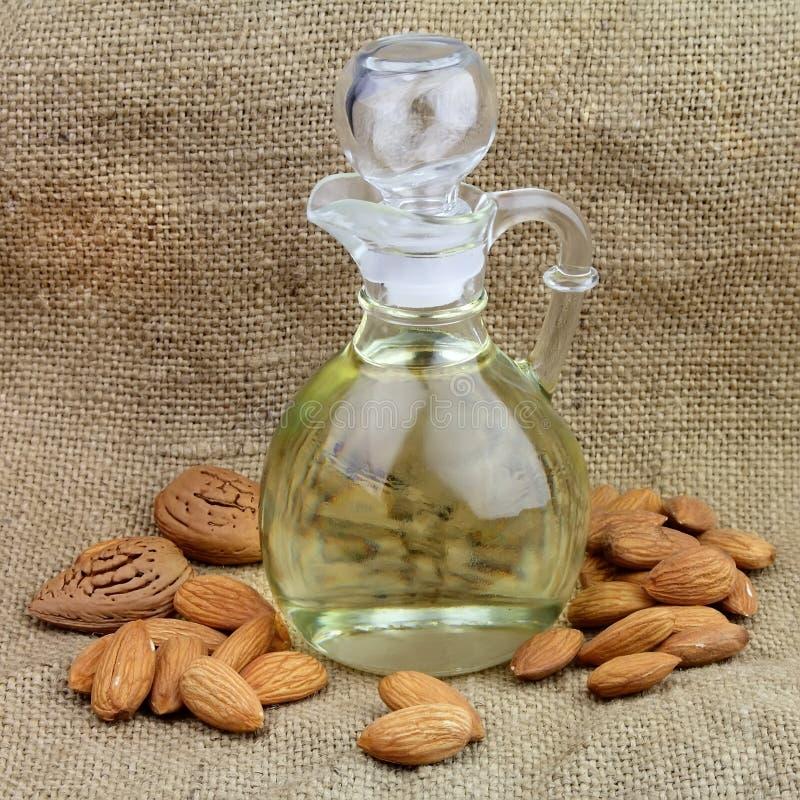 Una bottiglia dell'olio di mandorle con le noci immagini stock libere da diritti
