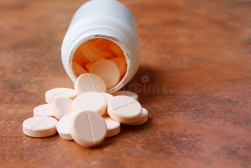 Una bottiglia delle pillole si è rovesciata sul pavimento fotografie stock libere da diritti