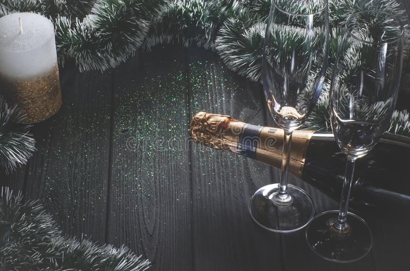 Una bottiglia di champagne e due vetri stanno su una tavola di legno grigio scuro circondata dalle decorazioni di Natale e da un  immagini stock libere da diritti