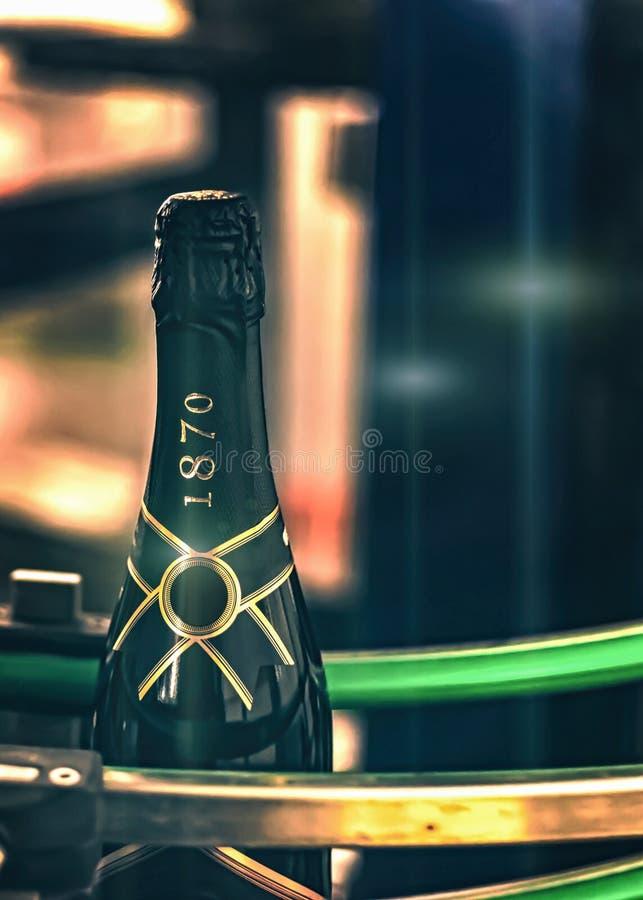 Una bottiglia di champagne sta muovendosi lungo il trasportatore alla fabbrica del vino spumante immagini stock