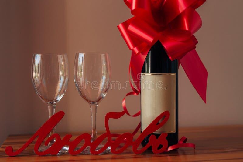 Una bottiglia di champagne sulla tavola e su due vetri vuoti fotografie stock