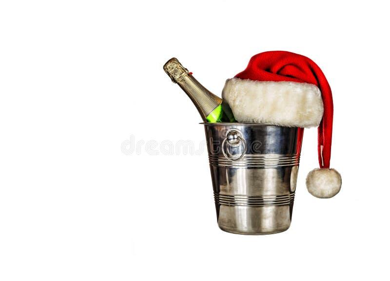 Una bottiglia di champagne in un secchiello del ghiaccio ed in un cappello di Santa Claus isolati su fondo bianco fotografie stock