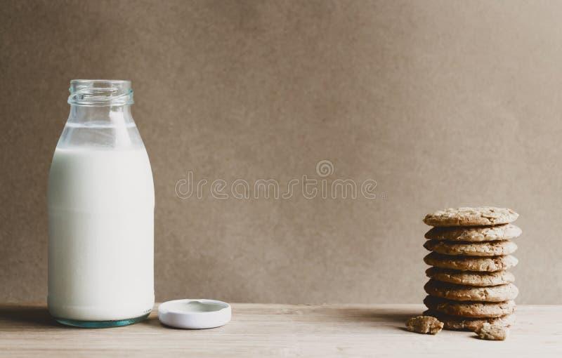 Una bottiglia di latte e dei biscotti fatti dell'avena sulla tavola di legno Con lo spazio della copia per il vostro testo fotografie stock