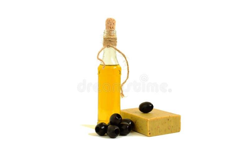 Una bottiglia di olio d'oliva, sapone verde oliva, olive su fondo bianco fotografie stock
