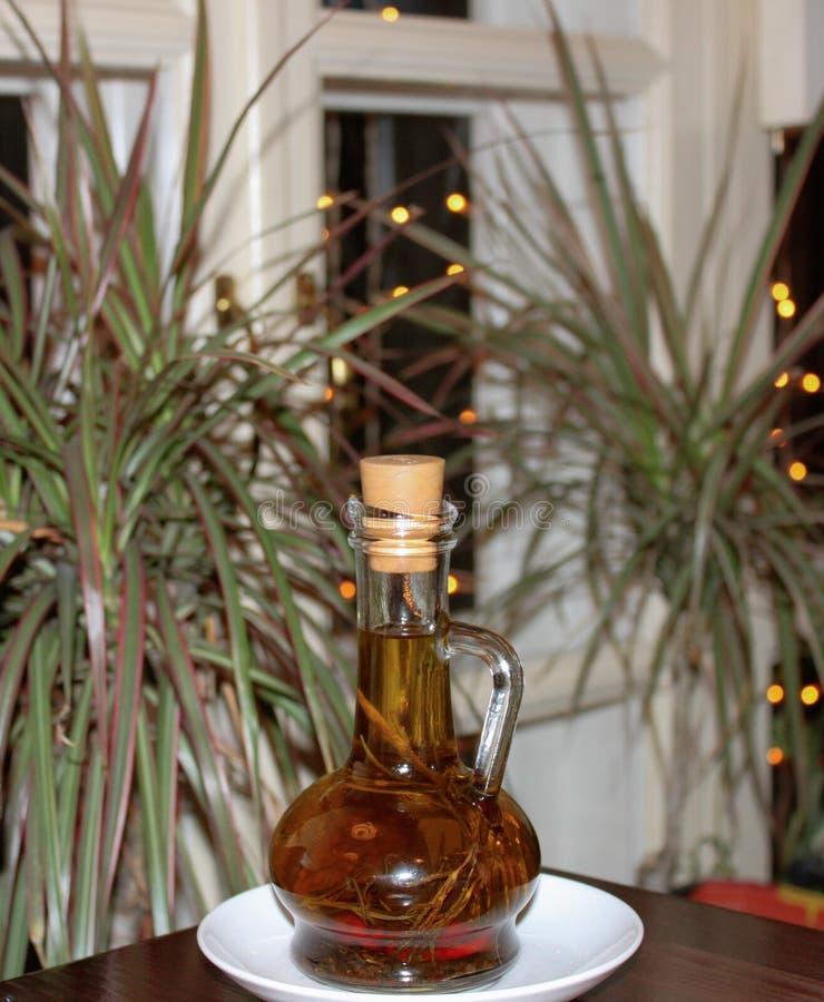 Una bottiglia di olio d'oliva sulla tavola con le piante su fondo fotografie stock libere da diritti