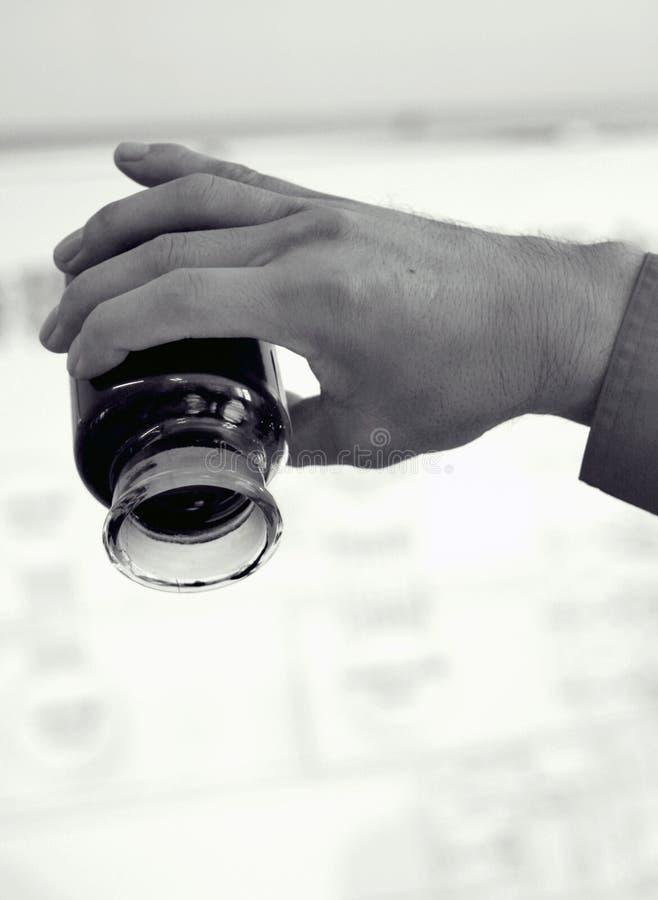 Una bottiglia di olio pesante in mano dei worker's fotografie stock libere da diritti