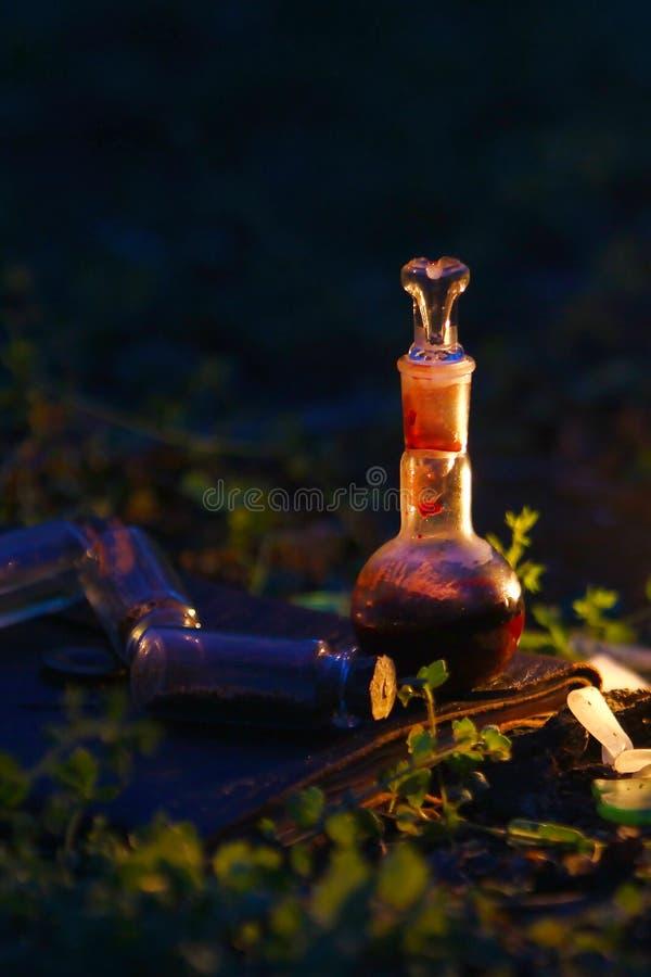 Una bottiglia di pozione su un fondo degli ingredienti magici fotografie stock libere da diritti