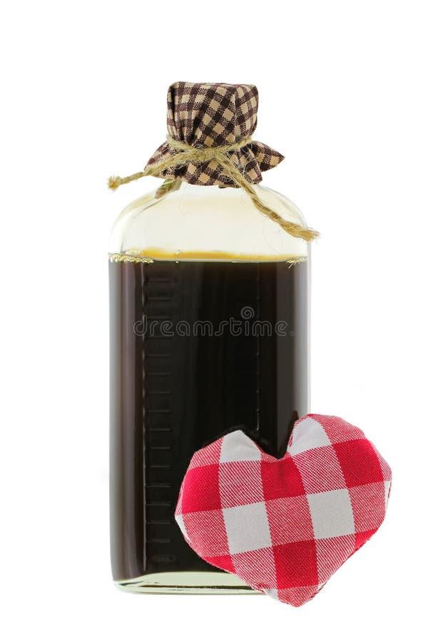 Una bottiglia di vetro della pozione di amore nel marrone con un cuore rosso del percalle immagini stock libere da diritti