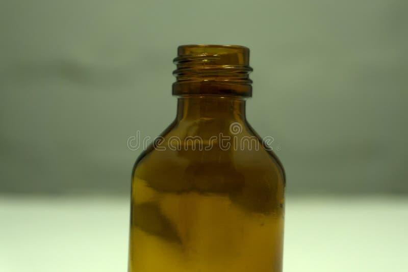 Una bottiglia di vetro della vecchia farmacia d'annata su un fondo vibrante di rosa di schiocco Fotografia minima di natura morta immagini stock libere da diritti